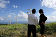 Business couple standing in a field of wind turbines