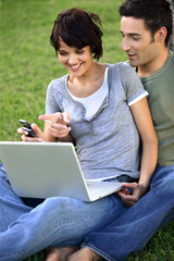 Couple sat in the park with laptop