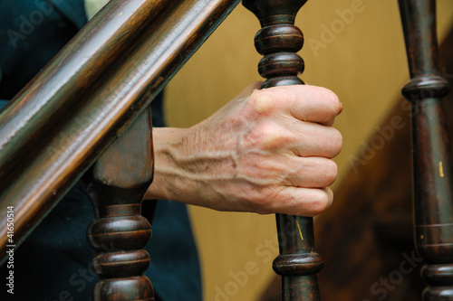 old woman wrinkled hands hold the handrail