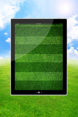 Blank digital PC tablet and  green field background