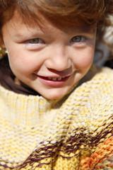 Little girl wearing jumper outdoors