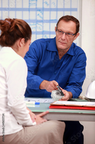 electrician advising woman on outlets