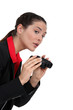 A businesswoman spying with binoculars.