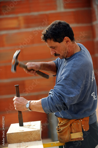 Worker using chisel and hammer on large block of wood