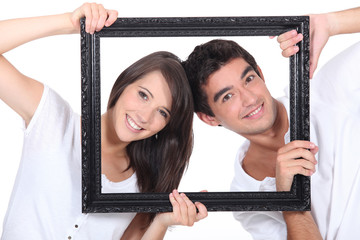 couple behind black frame