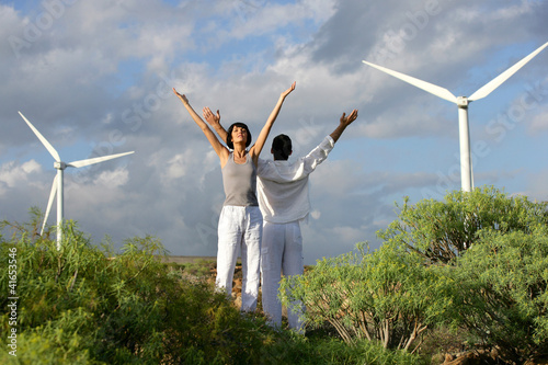 Couple stretching near wind turbines