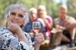 Senior woman enjoying a glass with friends on a picnic