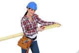 Female carpenter measuring a piece of wood.