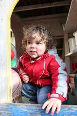 Little boy playing in garden shed