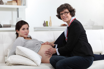Mother touching pregnant daughter's belly