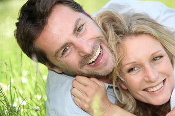 Couple laughing on the grass.