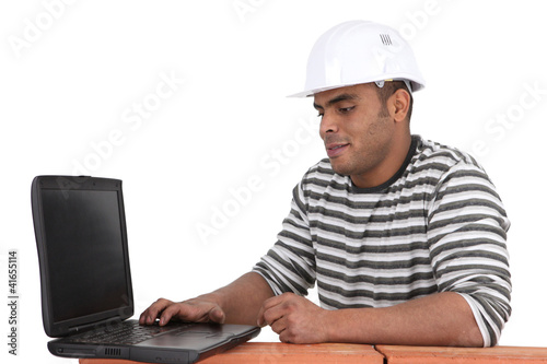 Builder sat using laptop