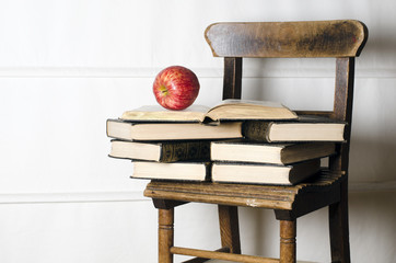 Child's vintage school chair supporting old books and apple.