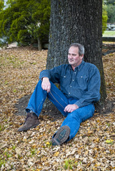 Working man wearing jeans and boots seated under tree