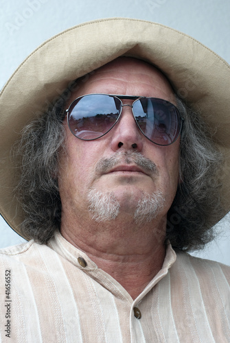 Middle-aged man wearing hat and sunglasses