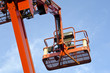 Orange construction crane baskets against blue sky