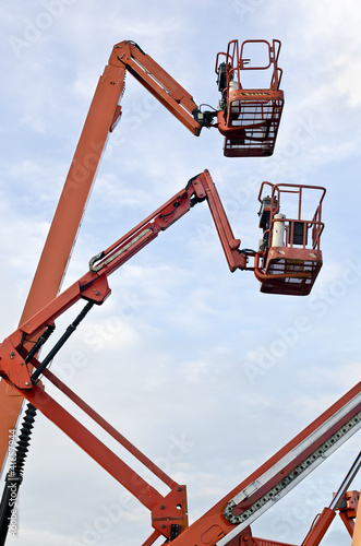 Orange construction crane baskets against blue sky