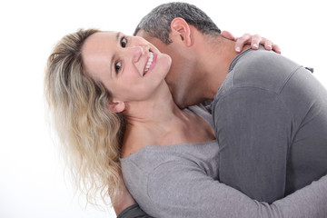 Man kissing his wife's neck
