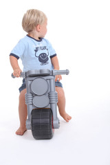 Child on a toy motorcycle
