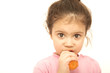 Little girl eating carrot over the white background