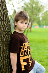 The boy near a tree in the park