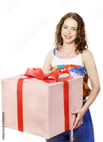The beautiful girl smiling holds a gift in a box