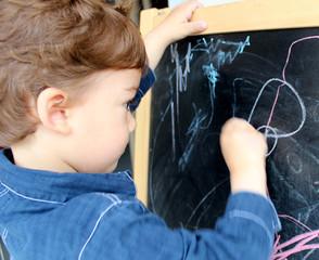 enfant dessinant à la craie sur un tableau