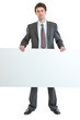 Full length portrait of businessman holding blank billboard