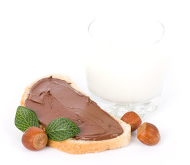 Chocolate spread container with a buttered toast, nuts and milk