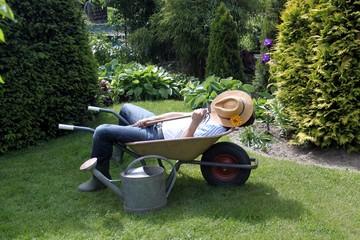 man mit Strohhut faulenzt in Schubkarre im Garten