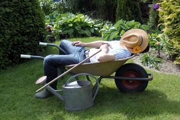 Gärtner entspannt in seiner Schubkarre mit Harke