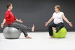 pregnant woman + personal trainer  on large stability balls