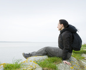 woman sitting on sea cliff
