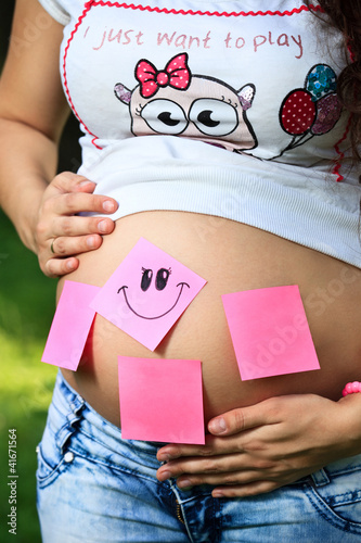 Pregnant girl with stickers on her belly holding it with both ar