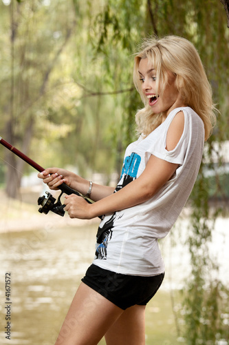 Pretty blonde girl with fishing rod laughing