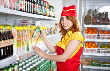 female the seller in the supermarket holding a box of juice