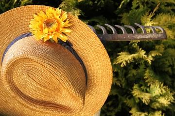Strohhut mit Blume hängt an rostiger Harke Garten