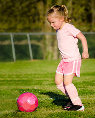Cute young girl in pink playing soccer on field