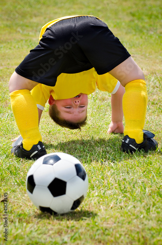 Young child watches soccer ball go through his legs