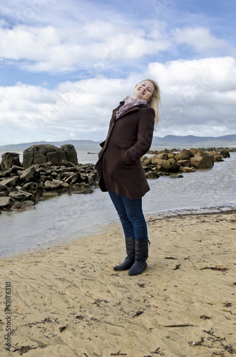 Attractive woman at Tasmanian beach in Winter coat