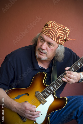 Mature guitarist with sunburst hollow body guitar and bandana