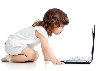 Funny kid girl looking at laptop. Side view, isolated on white b