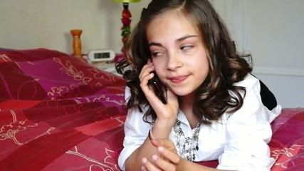 préado téléphonant sur son lit