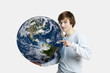 Handsome young man pointing and holding the planet earth