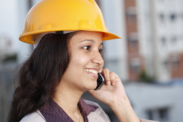 Smiling female construction engineer talking on mobile