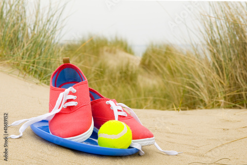 shoes, ball and frisbee on beach landscape