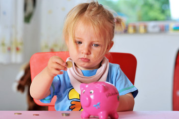 Kleinkind mit Sparschwein