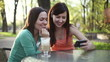 Two female friends with mobile phone in outdoors restaurant