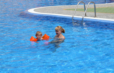 Girl with her mother in the swimming pool