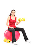 Smiling teenager lifting up a dumbbell seated on a fitness ball